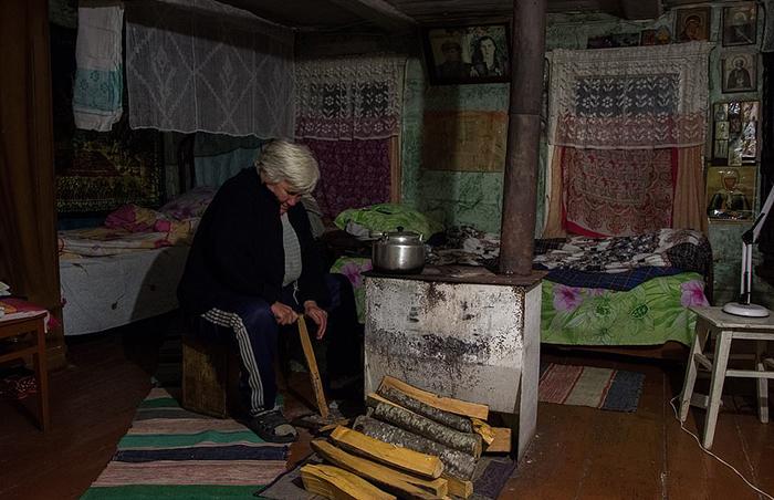 Люська откалывает лучину, чтобы зажечь печку.