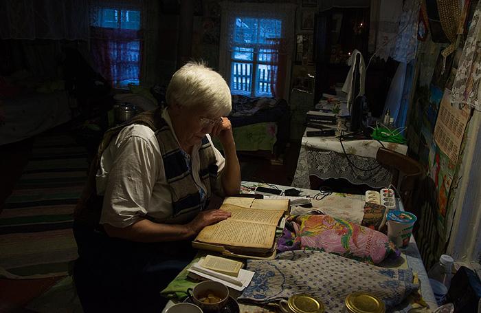 Люська читает старую книгу с молитвами.