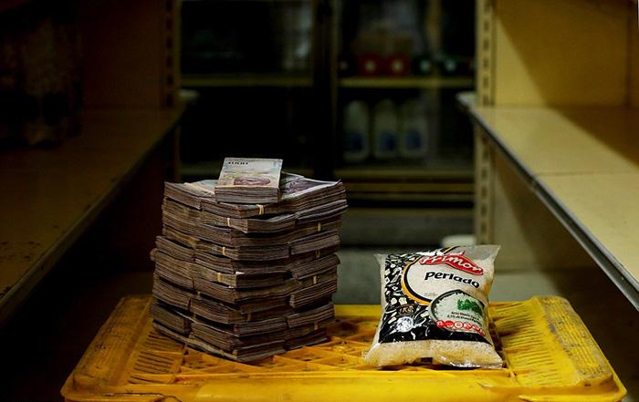 Килограммовая упаковка риса рядом с суммой денег, необходимой для его приобретения - 2 500 000 боливаров.