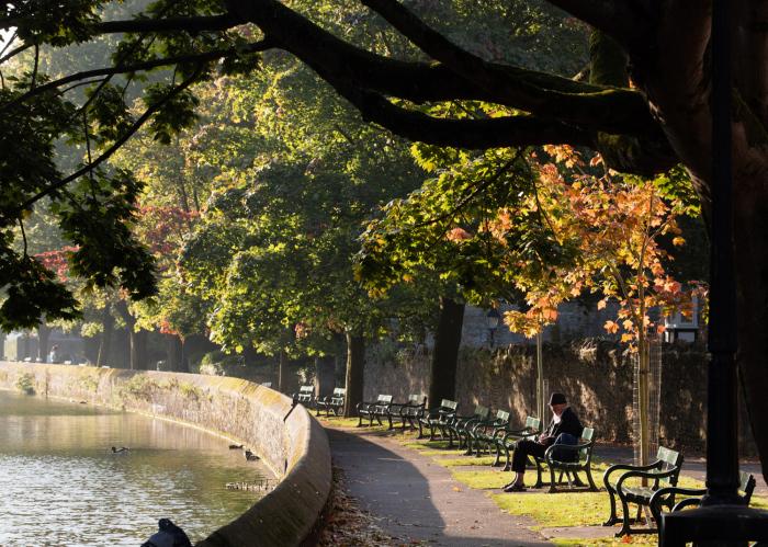 Мужчина сидит у воды. Англия, 1 октября 2015г.
