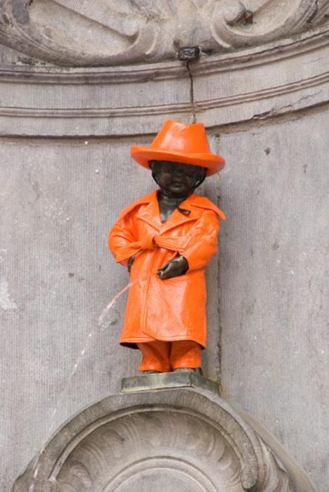 Статуя в оранжевом дождевом костюме.
