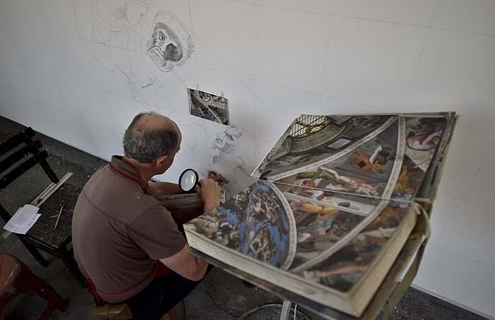 Волонтер Густаво Морено использует увеличительное стекло для воспроизведения деталей фрески.