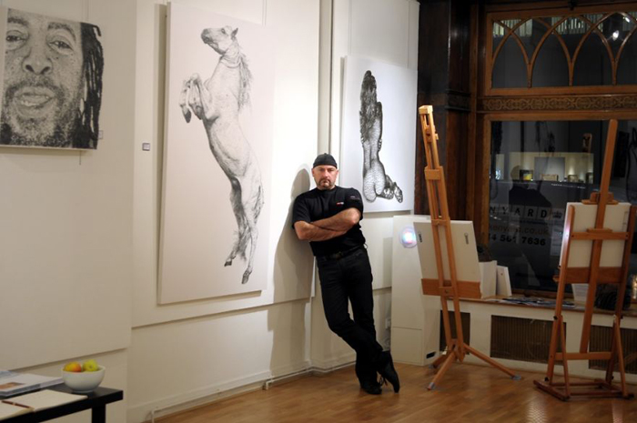 Маркус Левайн рядом с одной из своих картин.
