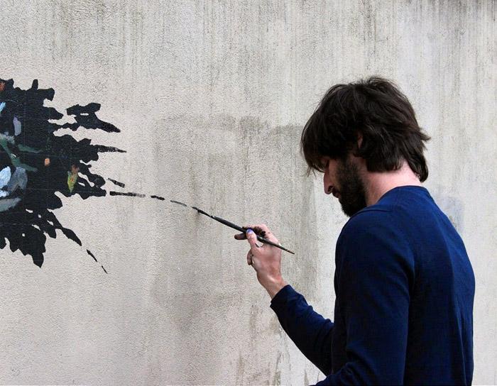 Испанский уличный художник Pejac в процессе создания работы «Вандал-изм».