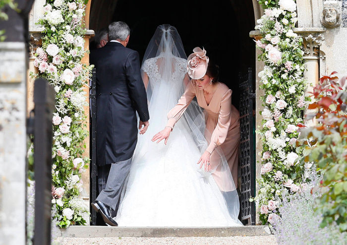 Кейт поправляет свадебное платье своей сестры.