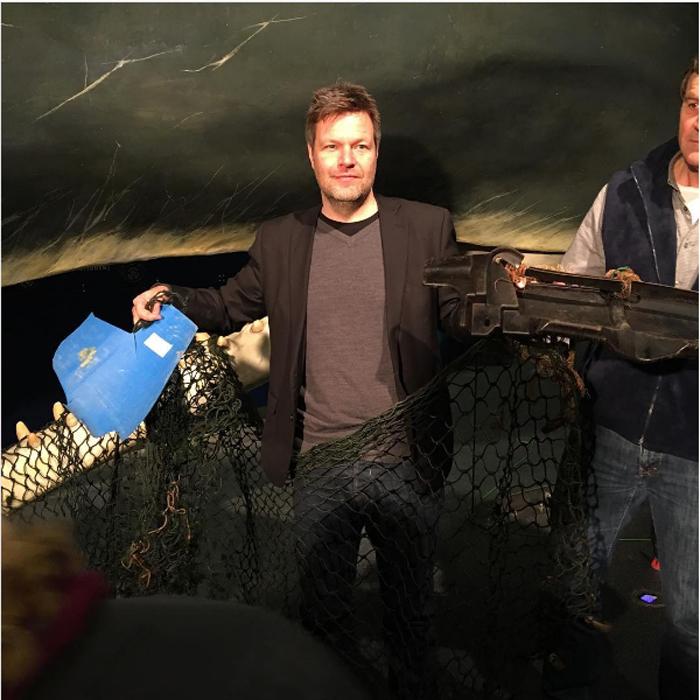 Роберт Хабек держит рыболовную сеть и часть мотора, найденные внутри кашалота.