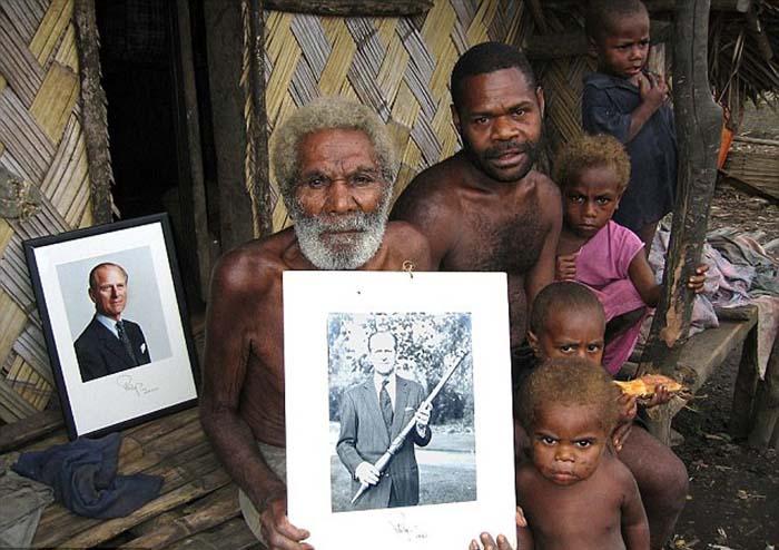 Жители Танна позируют с фотографиями принца Филиппа.