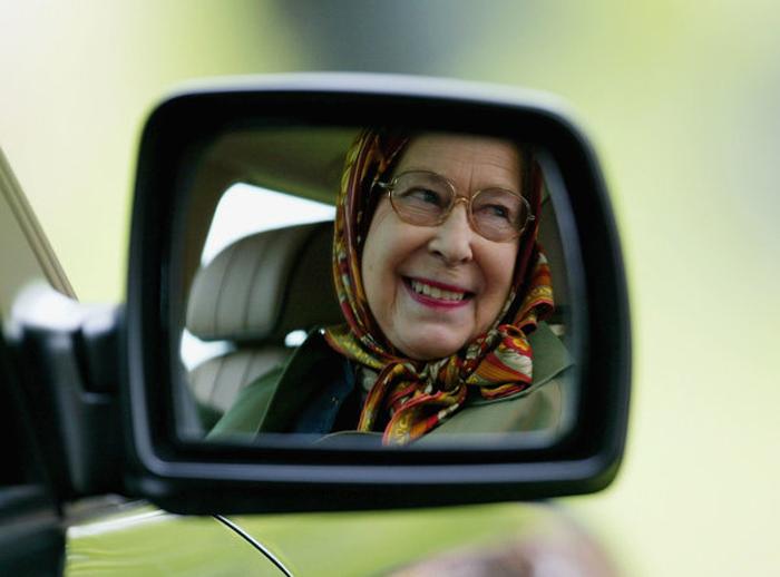 Елизавета Вторая следует на своей машине за своим супругом, Герцогом Эдинбургским, который в тот год соревновался на гонках гран-при.