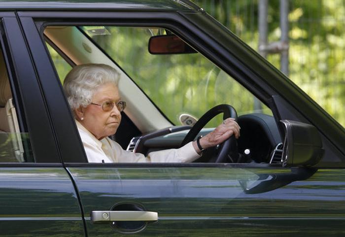 Елизавета Вторая наблюдает из своего автомобиля за гонками гран-при, проходящими в Виндзоре.