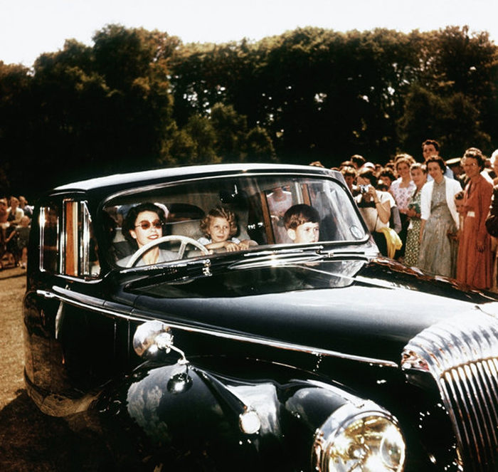 Королева Елизавета Вторая отвозит своих детей, принца Чарльза и принцессу Анну, в Виндзор в окружении зрителей.