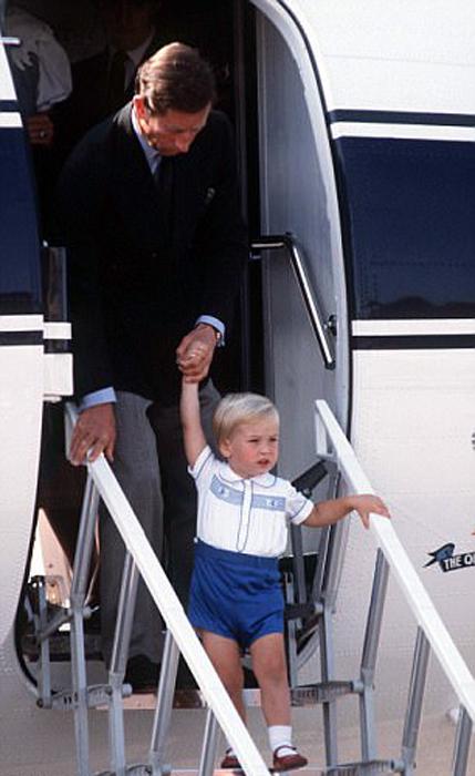 Принц Чарльз выходит из самолета вместе с сыном.