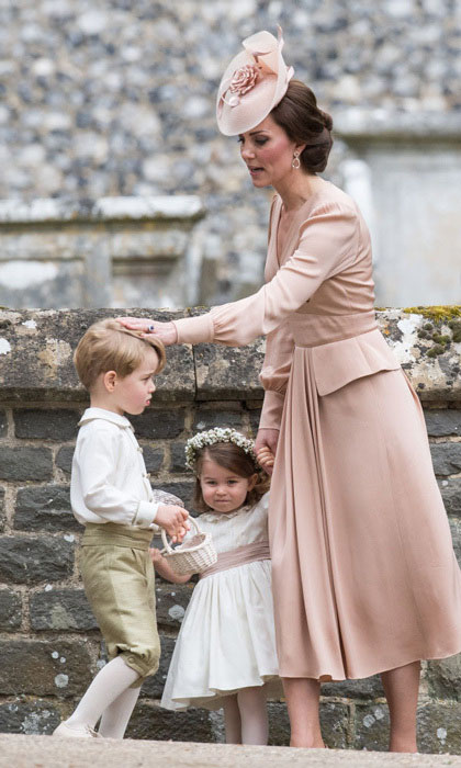 Кейт держит за руку двухлетнюю Шарлотту и поправляет прическу Джорджа. Перед началом свадьбы Пиппы, Кейт сказала, что единственное, о чем она беспокоится, это чтобы ее дети вели себя прилично.