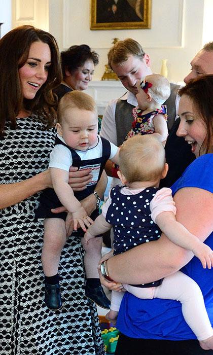 Герцогиня Кембриджская держит сына на руках, давая ему познакомиться с другим ребенком.