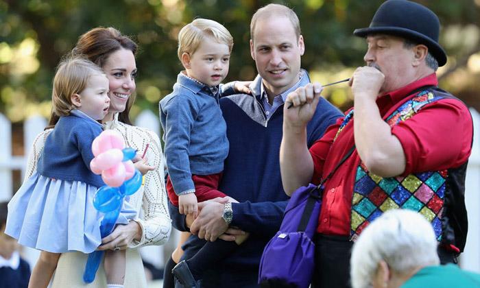 Кейт держит на руках Шарлотту в то время, как мужчина надувает шарик для принца Джорджа. Фото: Chris Jackson.