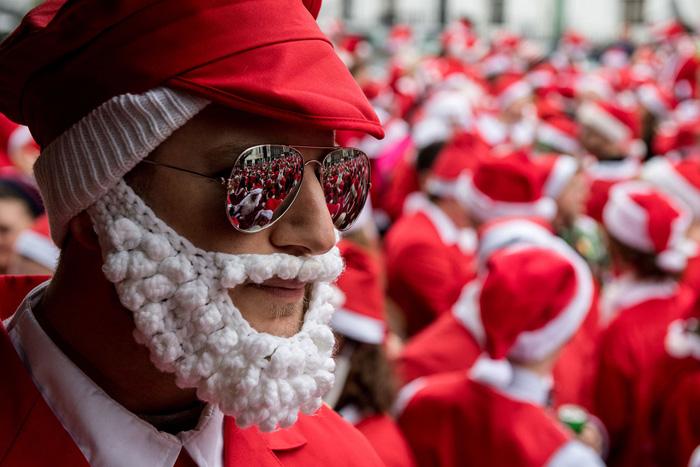 Толпа одетых в костюм Санты отражается в очках мужчины. Ежегодный СантаКон, 10 декабря 2016.