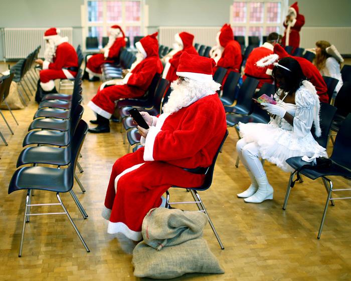 Люди в костюмах Санты и рождественских ангелов проводят время в ожидании, используя свои смартфоны. 26 ноября 2016.
