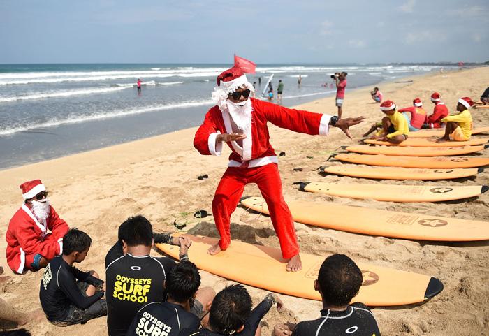 Серфер в легком костюме Санты показывает детям, как следует кататься на доске. 19 декабря 2016.