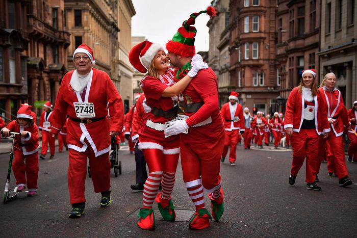 Парочка обнимается во время шествия Санта Клаусов к улице святого Винсента. 11 декабря 2016.