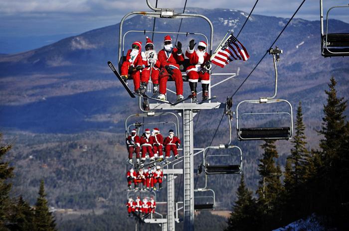 Лыжники одетые в костюмы Санты поднимаются к месту проведения благотворительного события Воскресенье Санты. 4 декабря 2016.