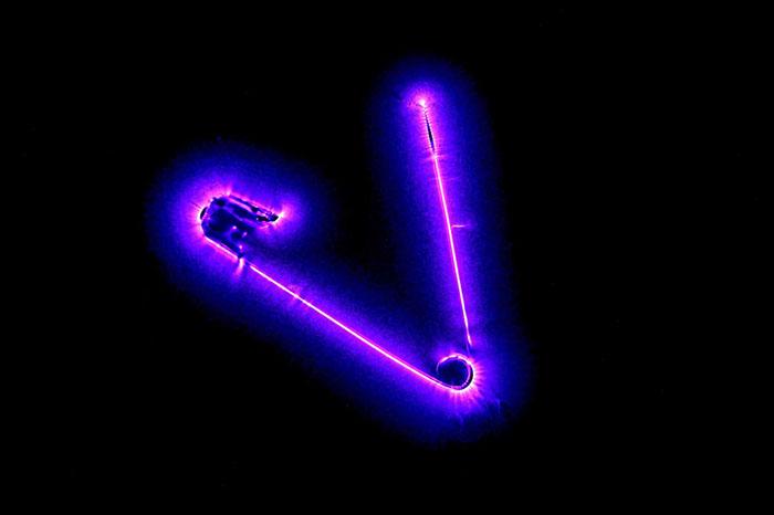 Ореол безопасности булавки, соединенной сгенератором переменного тока высокого напряжения, который генерирует свечение ореола вокруг булавки посредством ионизации иизлучения энергии ввиде фотонов. Фото: Richard Germain.