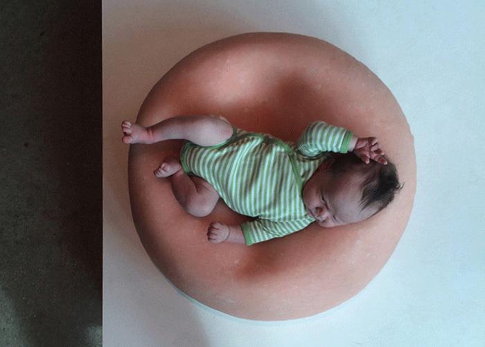 Ребенок лежит на одном из пуфов Гиги Баркер