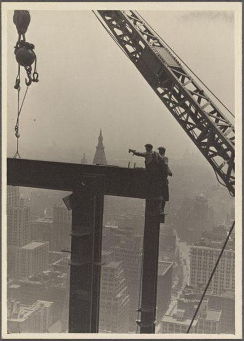 Два строителя на вершине балки, без страховки.
