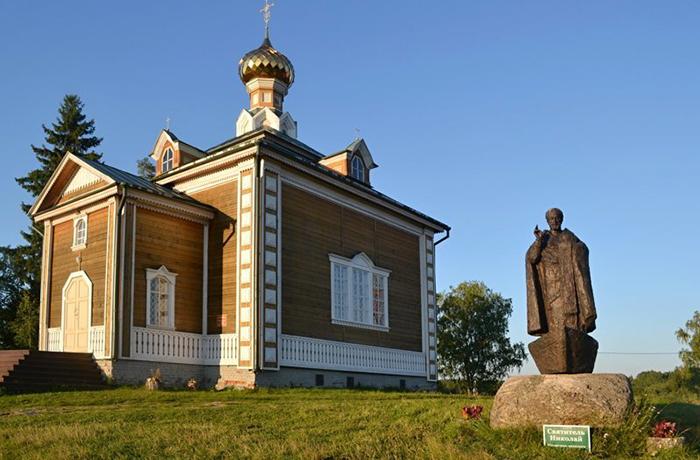 Деревянная церковь Николая Чудотворца и памятник святителю Николаю на лодке.