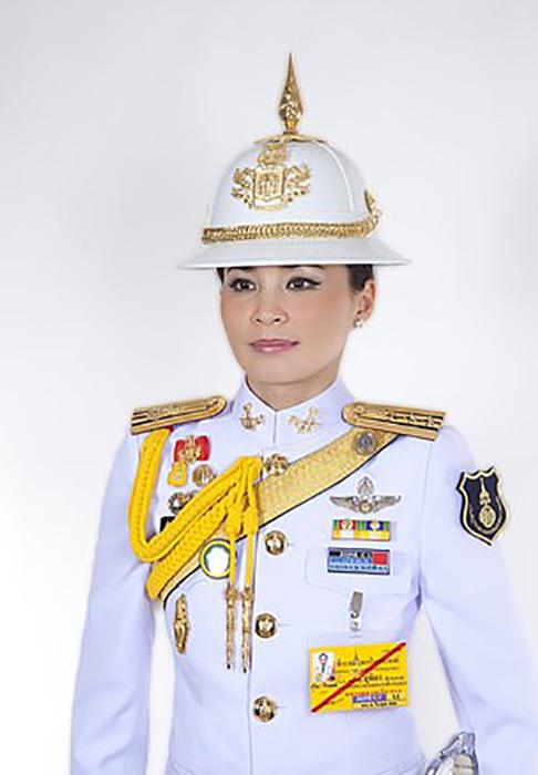 Королева позирует в белой военной форме, украшенной медалями.