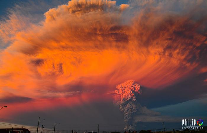 Заходящее солнце подсветило облако пепла красно-оранжевыми тонами.