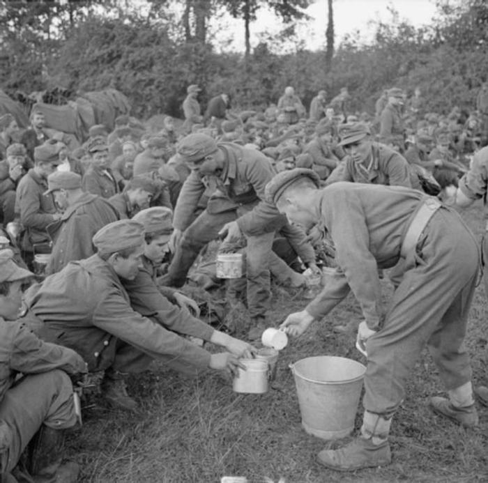 Британская армия в Нормандии - Солдат принес чай немецким пленным. 22 августа 1944г.