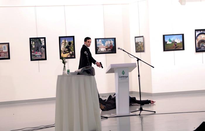 Мевлут Мерт Алтинтас стоит над Андреем Карловым, послом России в Турции, после стрельбы в фотогалерее Анкары, Турция. 19 дкабря 2016. Фото: Burhan Ozbilici.