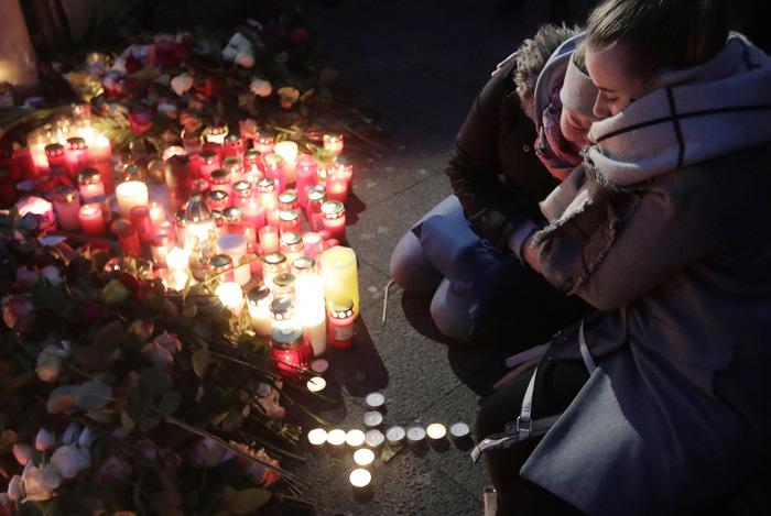 Две женщины горюют рядом со свечами, которые они принесли к месту трагедии на следующий день после того, как грузовик врезался в толпу. 20 декабря 2016. Фото: Markus Schreiber.