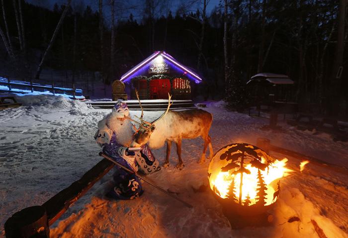 Мужчина в костюме Деда Мороза сидит у огня вместе с оленем по имени Якут недалеко от Красноярска. 21 декабря 2016. Фото: Ilya Naymushin.