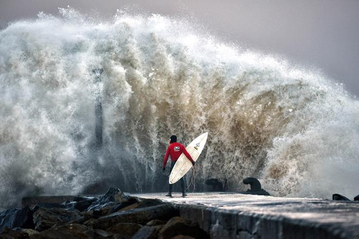 Огромная волна разбивается о пирс, на котором стоит профессиональный серфер Аль Менни. 22 декабря 2016. Фото: Charles McQuillan.