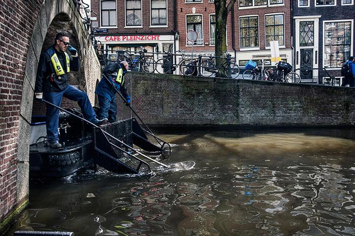 Городские службы очищают от мусора каналы Амстердама.