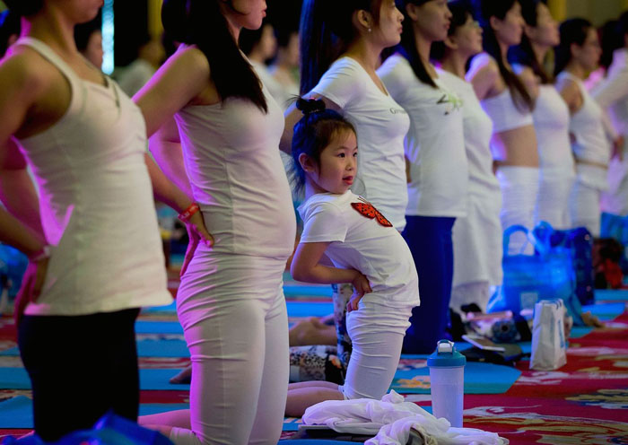 Ребенок выполняет йогу в Пекине, Китай. 21 июня 2015 г.