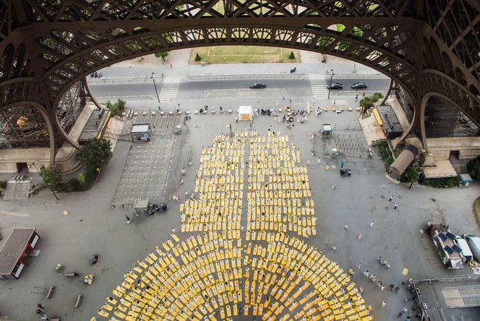 Тысячи участников одеты в белое выполняют асаны на желтых матрасах под Эйфелевой башней. Париж, Франция, 21 июня 2015 г.