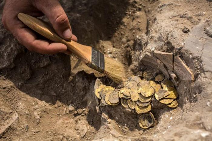 Израильский археолог Шахар Криспин чистит золотые монеты. Коллекция из 425 золотых монет, большинство из которых относится к периоду Аббасидов около 1100 лет назад.