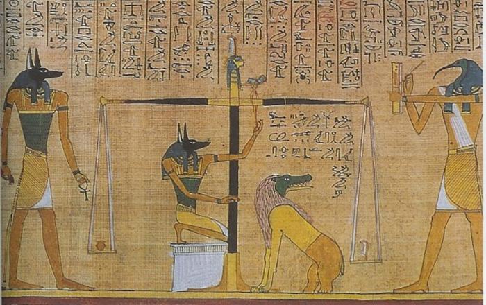 Бог Анубис (слева) наблюдает, как его слуги взвешивают деяния умершего. Бог Тот (справа, с головой ибиса) записывает результат. Древнеегипетское изображение.