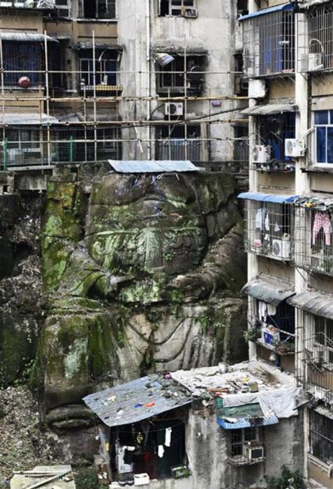 Статуя между двумя мнооквартирными домами в жилом комплексе в Чунцине на юго-западе Китая.