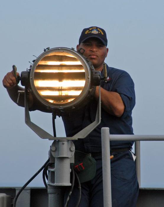 Квартирмейстер 2-го класса Тони Эванс из Хьюстона, штат Техас, посылает сигналы кода Морзе.