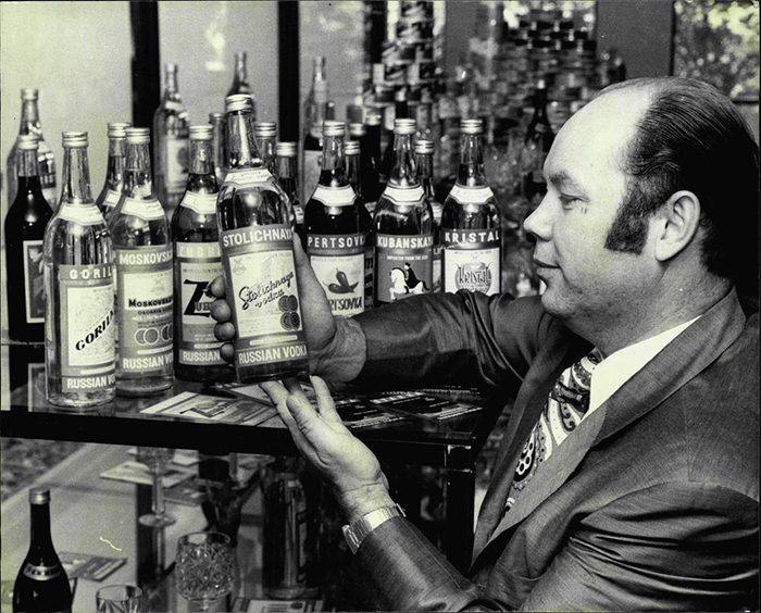 родавец показывает бутылку водки «Столичная».