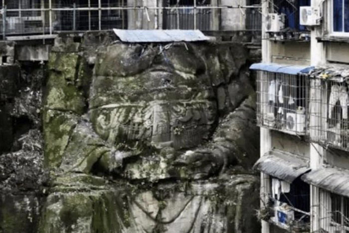 Древняя гигантская статуя Будды, поддерживающая многоквартирный дом.