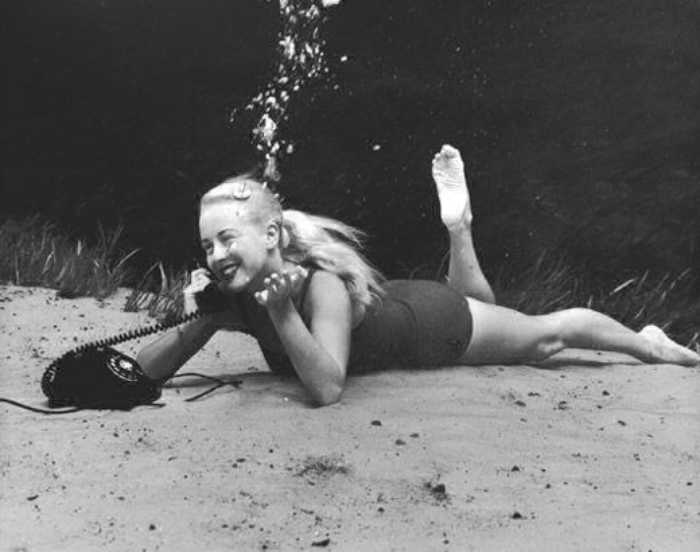 Молодая женщина разговаривает по телефону под водой.