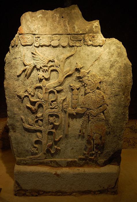 Эк Ахау - бог войны, торговли и какао у майя рядом с деревом какао.