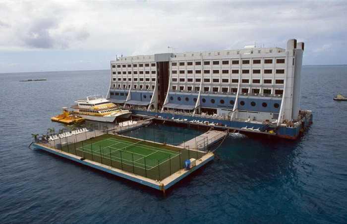 Семиэтажное здание плавучего отеля и теннисные корты.