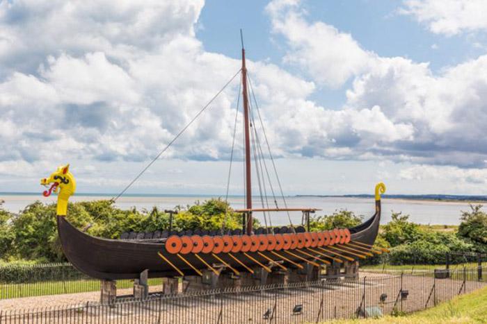 Восстановленное парусное судно или баркас викингов в заливе Пегуэлл в Кенте, Великобритания.