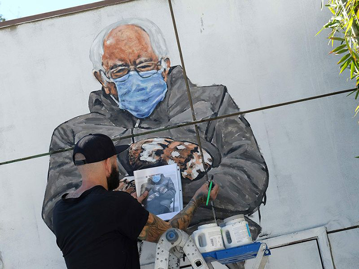 Художник создаёт мурал с изображением Берни Сандерса в варежках.
