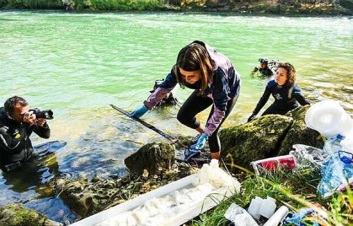 Археологи достают меч со дна реки.