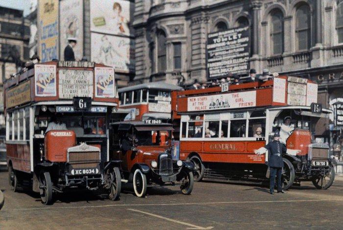 Регулировщик движения останавливает автобусы на Трафальгарской площади в Лондоне.